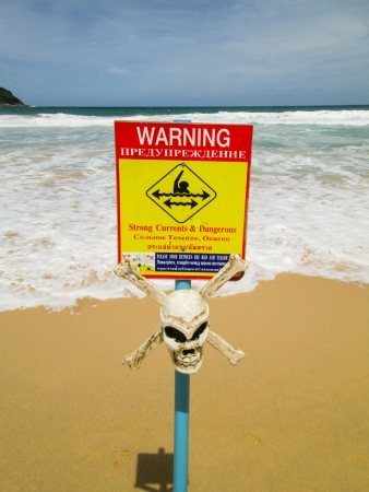 yellow sign post with skull is warning of dangerous currents on a beach  in Phuket, Thailand photo