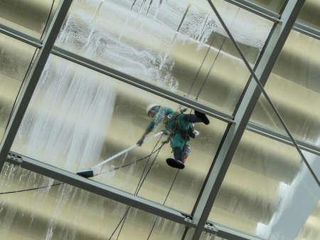 personal de limpieza: hombre está limpiando el techo de vidrio de un edificio con una lavadora a presión. rostro está oculto por una bufanda. Foto de archivo