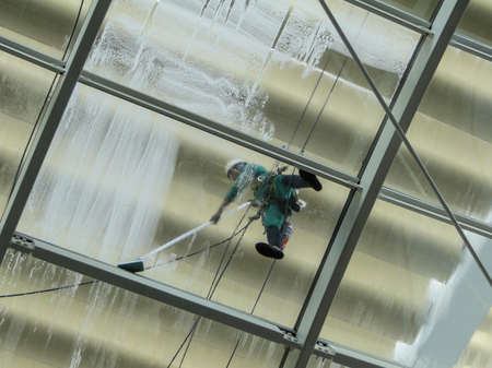 pressure washing: man is cleaning the glass roof of a building with a pressure washer. face is hidden by a scarf.