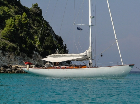 landlines: old gentlemens yacht (british flag) is anchoring and moored with landlines to the shore. lying in calm blue water of the adriatic sea in Croatia
