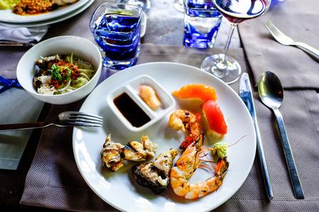 soja: assortiti sashimi e sushi di pesce servita su un piatto bianco con salsa di soia e wasabi