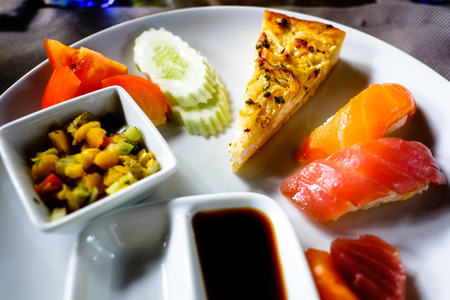 soja: assorted sashimi and sushi served on a white plate with soja and wasabi sauce.