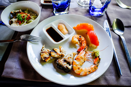 soja: assorted sashimi and sushi seafood served on a white plate with soja and wasabi sauce. Stock Photo