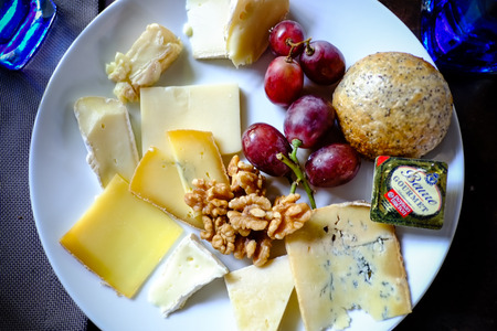 assorted cheese plate with grapes and walnut photo