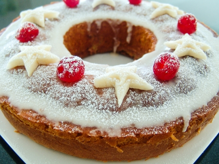 glace: ring cake decorated with sugar icing, marzipan stars and glace cherry. placed on a white plate. close-up