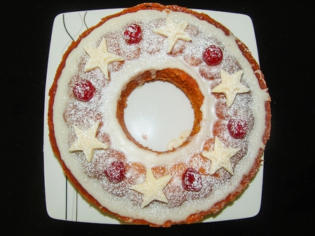 glace: ring cake decorated with sugar icing, marzipan stars and glace cherry. placed on a white plate on a black background. picture taken from top
