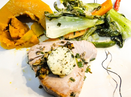 tuna steak with pak choi, carrot, pumpkin with garlic butter served on a white plate photo