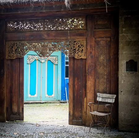 wood carving door: chair in front of an entrance to a balinese styled house Stock Photo