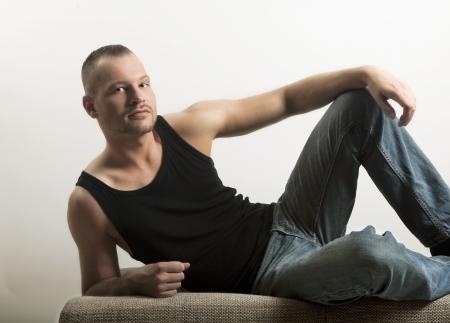 muscle shirt: joven tendido en un sof�, mirando a la c�mara, la camisa y los pantalones vaqueros del m�sculo, bien mantenido y construido, retrato, de tres d�as barba
