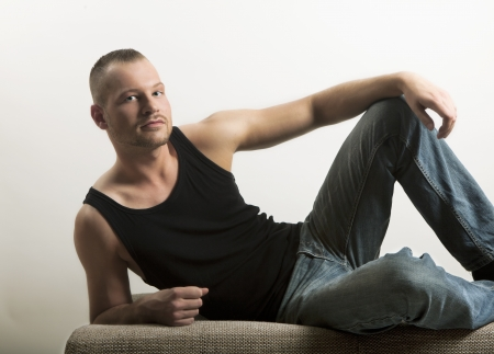 maintained: young man lying on a sofa, looking at the camera, muscle shirt and jeans, well maintained and built, portrait, three-day beard
