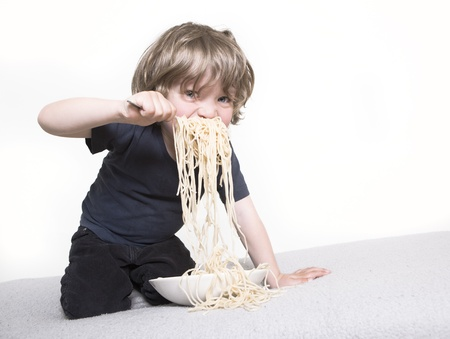 young boy eating his pasta on the couch