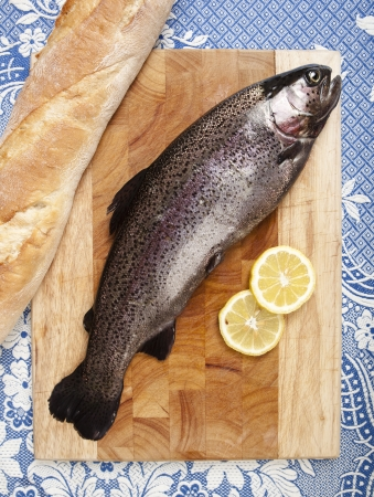 freshly caught trout, served on a wooden plank, served with bread and slices of lemon, close up, white tablecloth with blue pattern photo