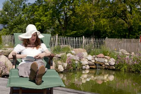woman with white hat lying on a garden lawn of wood in the background, a pond with beautiful shore photo