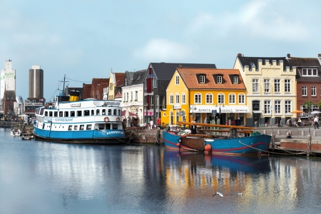 The old port of Husum with small and big ships, tourists and shops in the background