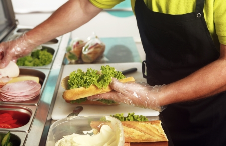 A chef preparing a sandwich with fresh salad, ham, cheese and butter  Close up of the hands holding the bread roll photo