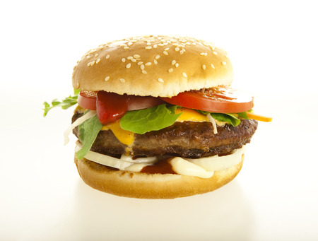 cheeseburger close up; background white; with tomato and beef Standard-Bild