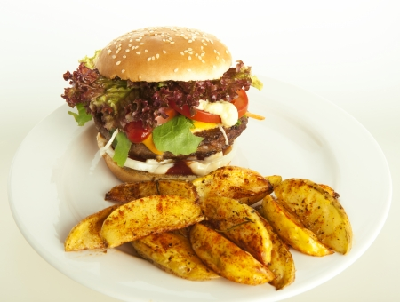 cheeseburger with potato wedges on plate; green and white striped tablecloth, tomatoes as decoration photo