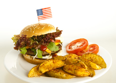 burger with potato wedges on plate; background white , tomatoes as decoration photo