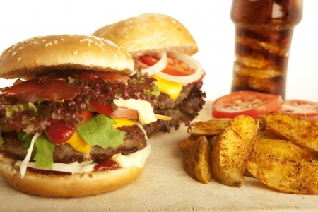 two burger with cola, potato wedges as garnish; background white photo