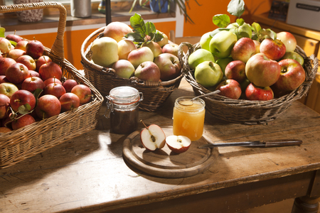 apple harvest, different varieties in baskets, arranged on a table, with honey and jam photo