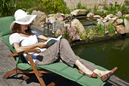 woman reads at the pond, relaxing on a garden lawn, in the background a beautiful rock garden
