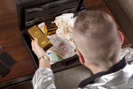 not full: man with suitcase full of money and gold, the suitcase standing on a table, the face is not visible Stock Photo