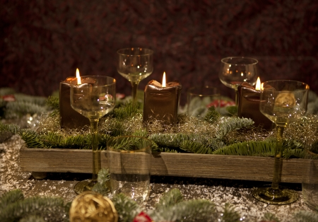 christmas place setting with candles, are wine glasses on the table, pine tree branches are adorned with decorative snow photo