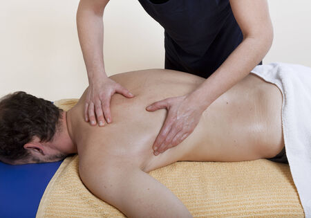 massaged: a physiotherapist treats a patient. the back is massaged
