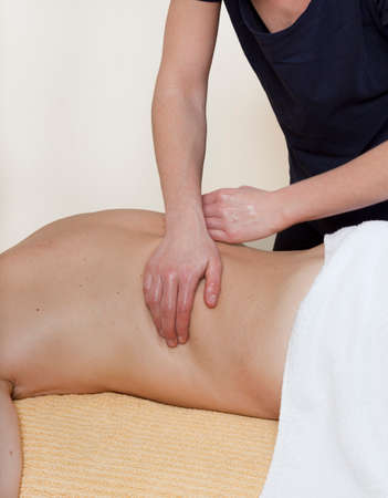 a physiotherapist treats a patient. the back is massaged photo