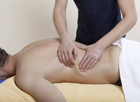 Massage therapy. a physiotherapist treats a patient. the back is massaged photo