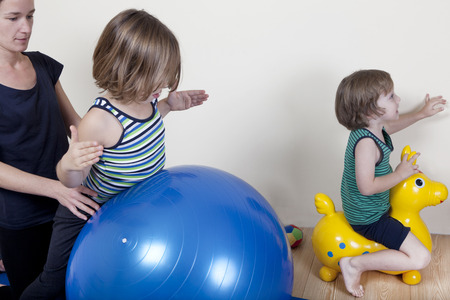 Children do gymnastics on a ball, a physical therapist shows exercises for the back