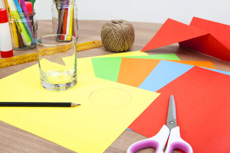 colored paper lying on a table. With a glass circles are painted and cut out photo