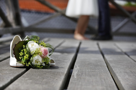 Bride with bridal bouquet white roses lying on the floor
