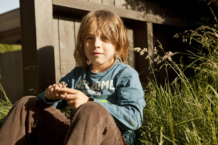 a boy with long brown hair sitting in garden