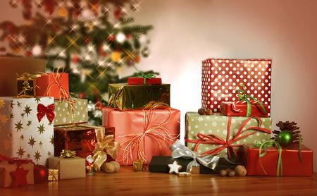 gift in celebration of a birth: muchos regalos de Navidad en una mesa en el fondo de un árbol de Navidad