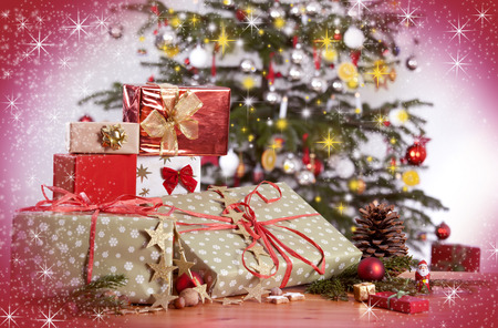 many gifts on a table and Christmas tree with red glittering background photo
