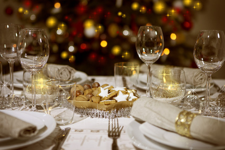 Festive table with christmas tree in the background Reklamní fotografie - 32462733