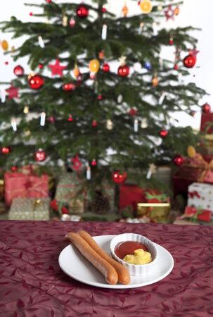 santa cena: dos salchichas con ketchup y mostaza en una mesa delante de un �rbol de Navidad Foto de archivo