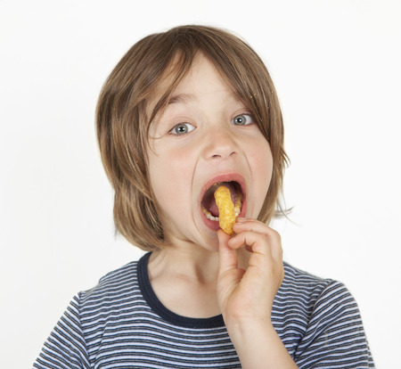 A boy with brown long hair shoves peanut flips in the mouth