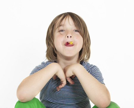 A boy with brown hair eating gummy bears, background white, isolated