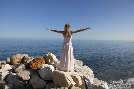 young woman at the sea standing on a rock and stretched out his arms in the air photo