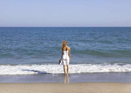 vacationer: Vacationer with brown long hair overlooking the sea Stock Photo