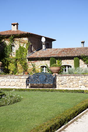 country house style: French Country House in classical style with vine plants and a green lawn