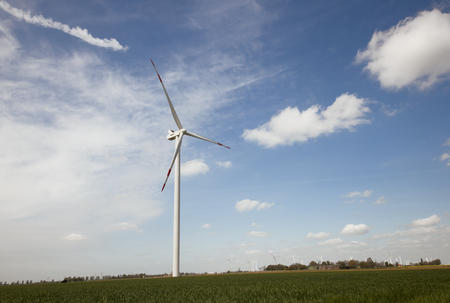 Power generation with a modern windmill against blue sky photo