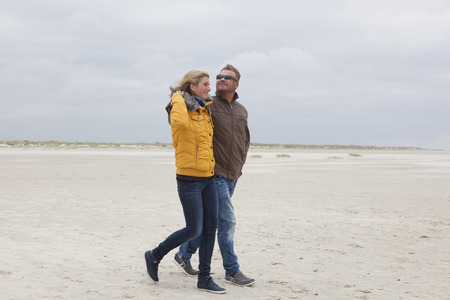 A young couple walks on the sandy beach in autumn photo