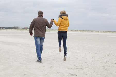 A young couple walks on the sandy beach in the winter photo