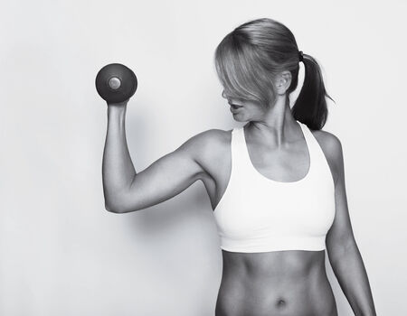 a woman in a white sports top trained their upper arms with dumbbells, black and white photo