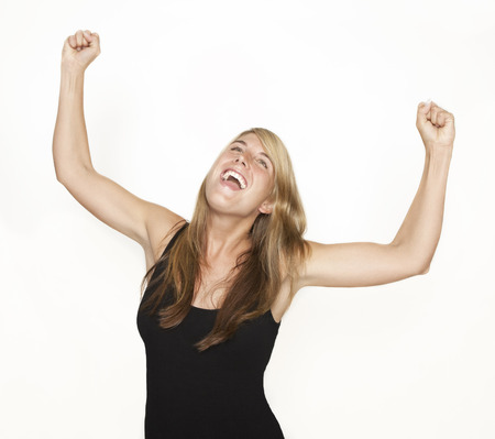 rejoices: A young woman exults and rejoices. She stretches her arms in the air. white background
