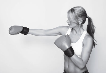 a young sporty woman with boxing gloves, black and white photo