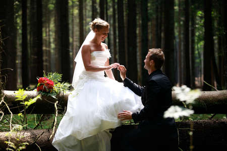 bride and groom shooting at the wedding in the forest photo